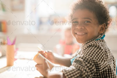 Cheerful schoolboy with rolled paper sitting by desk while making decoration