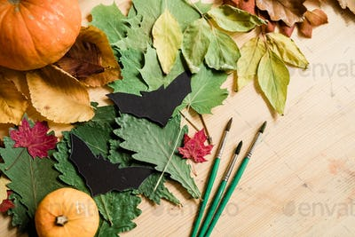 Composition of dry colorful leaves, gourds, handmade paper bats and paintbrushes