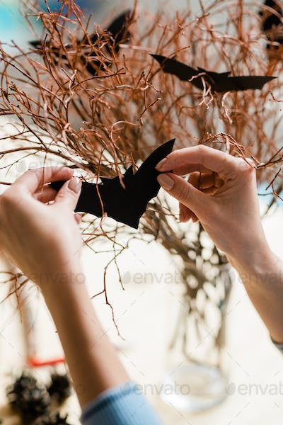 Human hands with black paper bat decorating dry branches for halloween