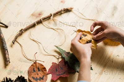 Hands of woman hanging dry leaves with drawn faces on stick over wooden table
