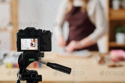 Creative woman in home camera recording soap making master class for subscribers
