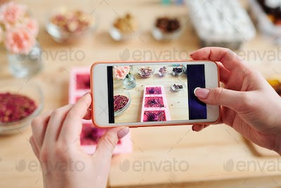 Hands of girl holding smartphone over table while taking photo of handmade soap
