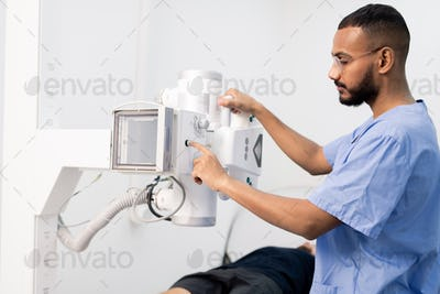 Young mixed-race man in blue uniform pressing button on new medical equipment