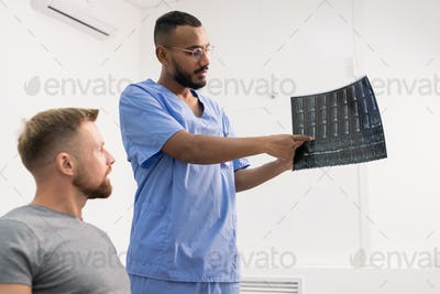 Radiologist in uniform pointing at one of fragments on x-ray of broken joint