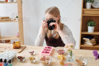 Young woman with photocamera photographing handmade soap and ingredients