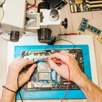 Overview of hands of professional repairman with soldering-irons during work
