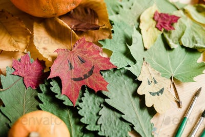 Background of dry autumn foliage, halloween faces on leaves and paintbrushes