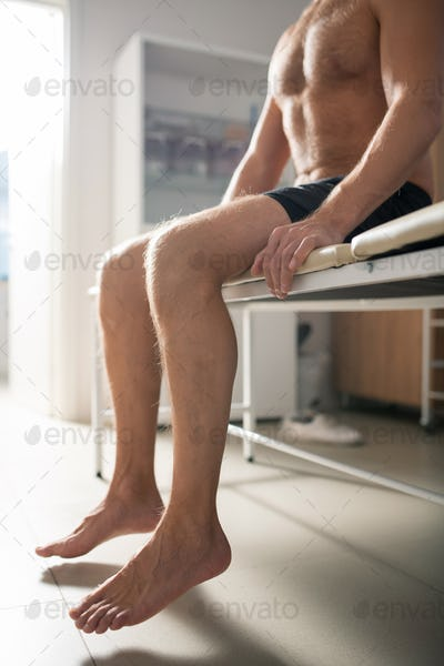 Bare legs of relaxed shirtless male patient sitting on couch in medical office