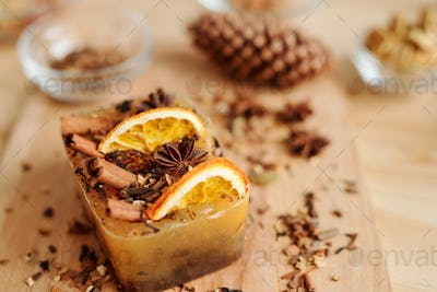 Handmade soap bar with aromatic spices and orange slices