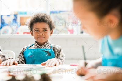 Cute schoolboy of African ethnicity in blue apron sitting by desks at lesson