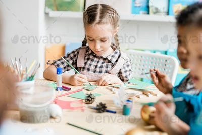 Young creative girl sitting by desk among classmates and painting paper firtree