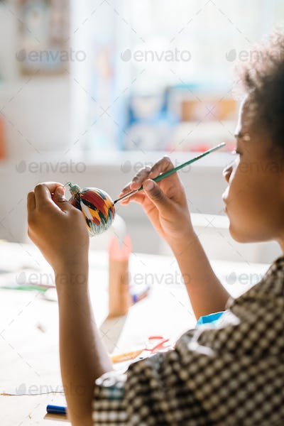 Diligent African pupil painting handmade decorative toy ball for holiday