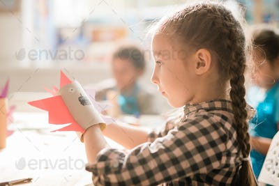 Cute schoolgirl with rolled paper sitting by desk and making scary halloween toy