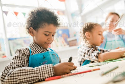Cute African schoolboy in blue apron using highlighter while drawing at lesson