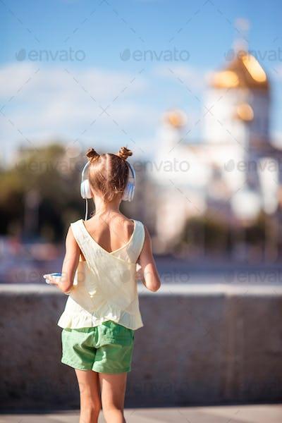 Little adorable girl listening music in the park