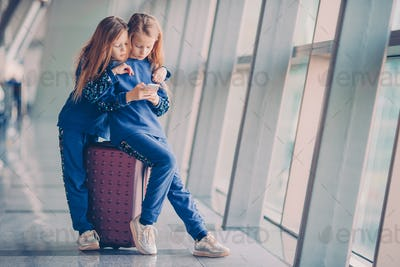 Little kids together in airport waiting for boarding