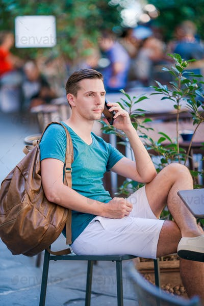 Caucasian boy is holding cellphone outdoors on the street. Man using mobile smartphone