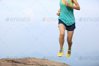 Successful woman runner running to mountain top