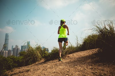Woman running on dirt mountain trail with modern city in the distance