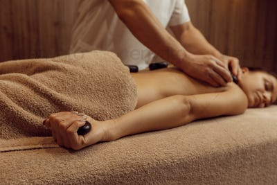Male masseur puts stones on back of slim woman