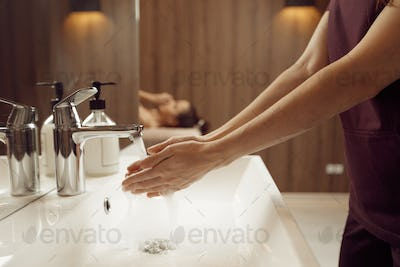 Female masseur washes her hands before massage