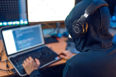 Hacker in the hood sitting at laptop, back view