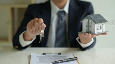 The house broker holds the keys and the model house in hand. Real estate concept.