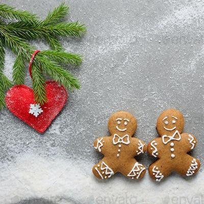 Flat lay at two gingerbread men having a walk on snow under fir