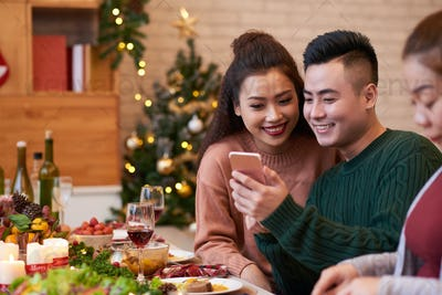 Couple with smartphone at dinner table