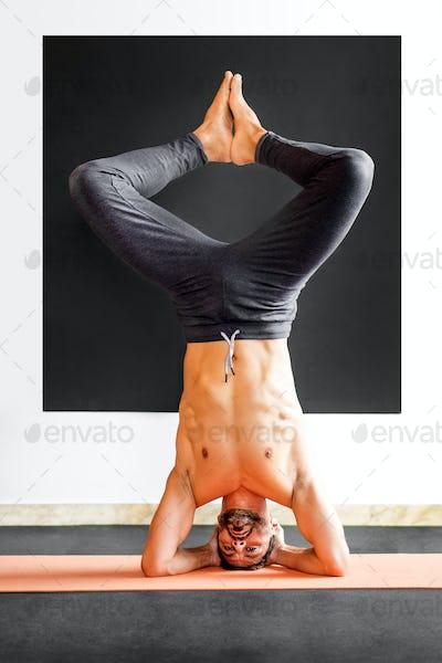 Muscular man doing a variation sirsasana headstand