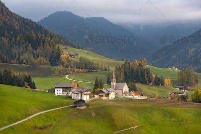Green alpine valley with view of Santa Maddalena village church,
