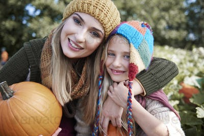 Portrait of mom and daughter with pumpkin