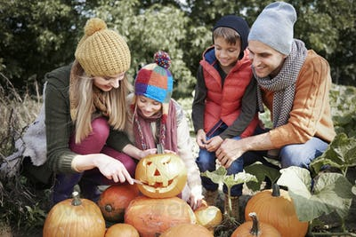 Parents with child preparing to pumpkin for Halloween