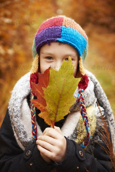 Boy covering face with autumn leaf