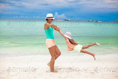 Young beautiful mother and her adorable little daughter have fun at tropical beach