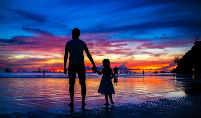 Father and daughter silhouettes in sunset at the beach on Boracay