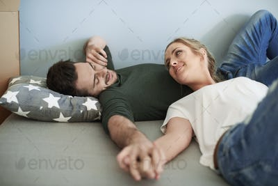 Woman and man having rest during moving house