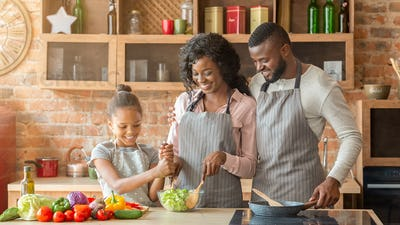 Young parents teaching their daughter how to make salad