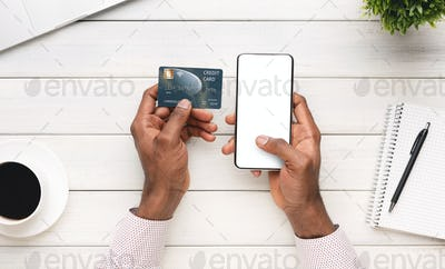 Businessman paying his bills online using smartphone with blank screen