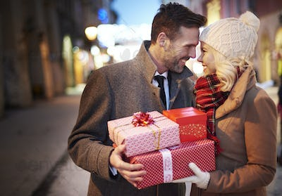 Affectionate couple with stack of presents