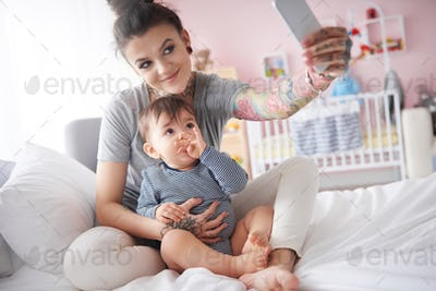 Young mother taking self portrait with smartphone