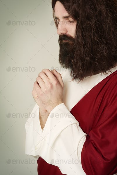 Studio shot of praying Jesus in concentration
