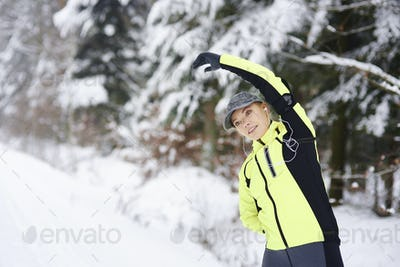 Woman stretching her arms and hands in winter forest