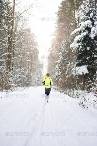 Rear view of woman running in winter forest
