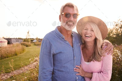 Portrait Of Loving Mature Couple In Countryside Hugging Against Flaring Sun