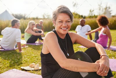 Portrait Of Mature Woman On Outdoor Yoga Retreat With Friends And Campsite In Background