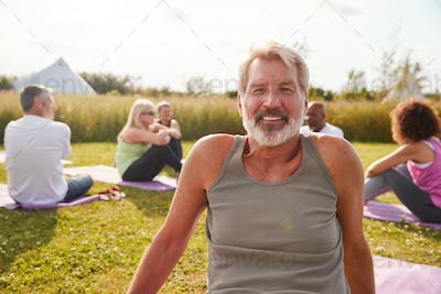 Portrait Of Mature Man On Outdoor Yoga Retreat With Friends And Campsite In Background