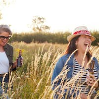 Group Of Mature Female Friends Walking Through Field On Camping Vacation Drinking Beer