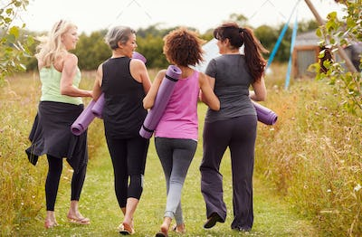 Rear View Of Mature Female Friends On Outdoor Yoga Retreat Walking Along Path Through Campsite