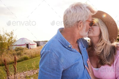 Loving Mature Couple In Countryside Kissing Against Flaring Sun
